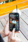 Smartphone και καφές παιχνιδιού χεριών γυναικών στον ξύλινο πίνακα Στοκ Εικόνες