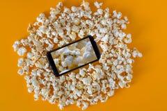 Smartphone και popcorn στον κίτρινο πίνακα Έννοια τεχνολογίας κινηματογράφος σε ένα smartphone με το υπόβαθρο popcorn στοκ εικόνα