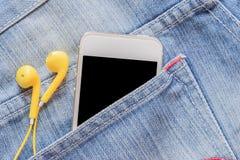 Smartphone κινηματογραφήσεων σε πρώτο πλάνο και κίτρινο ακουστικό στην τσέπη τζιν τζιν Στοκ Εικόνες