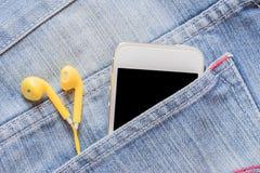 Smartphone κινηματογραφήσεων σε πρώτο πλάνο και κίτρινο ακουστικό στην τσέπη τζιν τζιν Στοκ Φωτογραφία