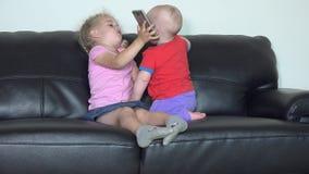Smartphone μεριδίου κοριτσιών αδελφών με την λίγος αδελφός απόθεμα βίντεο