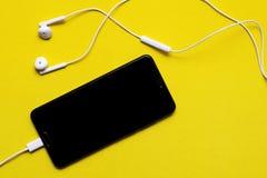 Smartphone με τα ακουστικά στο υπόβαθρο χρώματος Κινηματογράφηση σε πρώτο πλάνο του έξυπνου τηλεφώνου με τα ακουστικά σε ένα κίτρ στοκ φωτογραφία με δικαίωμα ελεύθερης χρήσης