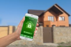 Smartphone με την εγχώρια ασφάλεια app σε ένα χέρι στο υπόβαθρο οικοδόμησης Στοκ φωτογραφίες με δικαίωμα ελεύθερης χρήσης