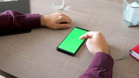 Smartphone με την πράσινη χλεύη χρώματος οθόνης επάνω σε ετοιμότητα τον πίνακα και αρσενικά που λειτουργούν σε το απόθεμα βίντεο