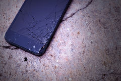 Smartphone με τη σπασμένη οθόνη αφής στο τσιμεντένιο πάτωμα Στοκ Εικόνες