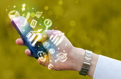 Smartphone με τη χρηματοδότηση και τα εικονίδια και τα σύμβολα αγοράς Στοκ Φωτογραφίες