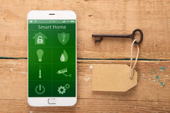 Smartphone με το έξυπνο σπίτι app στο ξύλινο γραφείο Στοκ εικόνα με δικαίωμα ελεύθερης χρήσης
