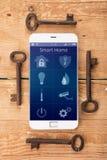 Smartphone με το έξυπνο σπίτι app στο ξύλινο γραφείο Στοκ Εικόνες