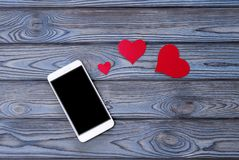 Smartphone, μορφή καρδιών όμορφη μεγάλη εκμετάλλευση καρδιών κοριτσιών brunette ανασκόπησης απομόνωσα τις κόκκινες λευκές νεολαίε Στοκ φωτογραφίες με δικαίωμα ελεύθερης χρήσης