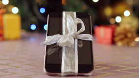 Smartphone μπροστά από το χριστουγεννιάτικο δέντρο απόθεμα βίντεο