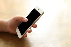 Smartphone προτύπων εκμετάλλευσης γυναικών στο γραφείο ξύλινο Στοκ Εικόνες