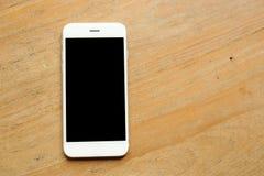 Smartphone προτύπων εκμετάλλευσης χεριών στο γραφείο ξύλινο Στοκ Φωτογραφία