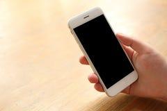 Smartphone προτύπων εκμετάλλευσης χεριών στο γραφείο ξύλινο Στοκ εικόνα με δικαίωμα ελεύθερης χρήσης