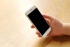 Smartphone προτύπων εκμετάλλευσης χεριών στο γραφείο ξύλινο Στοκ Εικόνες