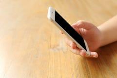 Smartphone προτύπων εκμετάλλευσης χεριών στο γραφείο ξύλινο Στοκ φωτογραφίες με δικαίωμα ελεύθερης χρήσης