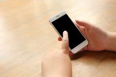 Smartphone προτύπων εκμετάλλευσης χεριών στο γραφείο ξύλινο Στοκ Φωτογραφίες