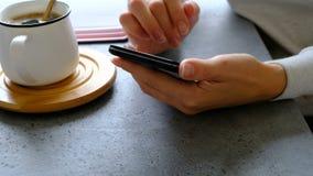 Smartphone στα χέρια, τον καφέ και το σημειωματάριο της γυναίκας σε έναν πίνακα κλείστε επάνω απόθεμα βίντεο