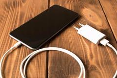 Smartphone στη δαπάνη Στον ξύλινο πίνακα o στοκ εικόνα με δικαίωμα ελεύθερης χρήσης