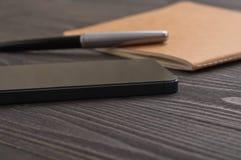 Smartphone στον εργασιακό χώρο γραφείων με το σημειωματάριο στοκ εικόνες