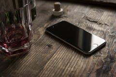 smartphone στον ξύλινο πίνακα με το ουίσκυ Στοκ φωτογραφία με δικαίωμα ελεύθερης χρήσης
