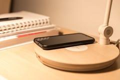 Smartphone στο μαύρο ραδιόφωνο χρέωσης περίπτωσης στον πίνακα κρεβατιών Στοκ φωτογραφία με δικαίωμα ελεύθερης χρήσης