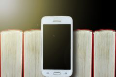 Smartphone στο υπόβαθρο των βιβλίων Σκοτεινή ανασκόπηση, διάστημα αντιγράφων Έννοια: βιβλία και ηλεκτρονικές συσκευές στοκ φωτογραφία με δικαίωμα ελεύθερης χρήσης