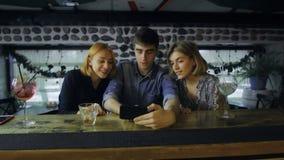Φίλοι που χρησιμοποιούν το smartphone στο μετρητή φραγμών στο μπαρ απόθεμα βίντεο