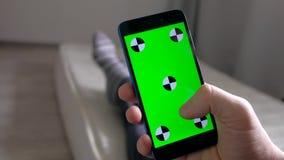 Smartphone χρήσης προσώπων χεριών με την πράσινη οθόνη που βρίσκεται στο στρώμα στο δωμάτιο φιλμ μικρού μήκους