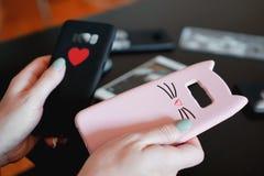 Руки держа красочные случаи смартфона Выберите между черным и розовым случаем стоковое фото