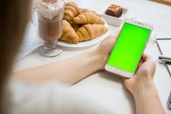 Smartphone в руках зеленого экрана в кафе, умный телефон с экраном зеленого цвета ключа chroma на белой предпосылке Стоковые Фотографии RF