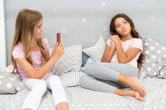 Smartphone девушек представляя большую съемку Пошлите фото социальную сеть используя smartphone Smartphone для развлечений малыши стоковое фото
