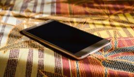 Smartphone золота лежа на одеяле Стоковые Изображения