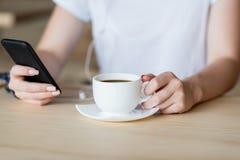 Smartphone и чашка кофе в женских руках Стоковое Фото