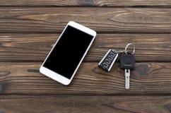 Smartphone, ключи автомобиля на предпосылке Стоковая Фотография