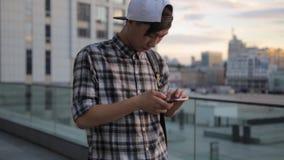 Smartphone красивого азиатского человека студента печатая городская городская ноча освещает отправку СМС приема техники связи 4g видеоматериал