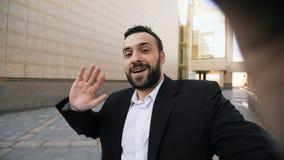Smartphone молодого бородатого бизнесмена говоря имея онлайн видео- деловую встречу болтовни outdoors Стоковые Фотографии RF