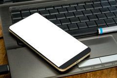 Smartphone на клавиатуре, деле и работе онлайн Стоковые Фотографии RF