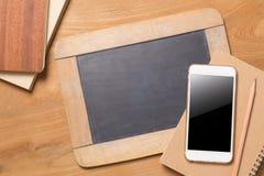 Smartphone, доска, карандаш, тетради на backgr деревянного стола Стоковая Фотография