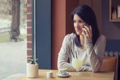 Smartphone пользы молодой женщины на кафе Стоковое Изображение RF