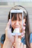 Smartphone принимая девушку ест мороженое Стоковая Фотография