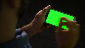 Smartphone при зеленый экран, который держит в руке человек делая удар и сигнал показывать видеоматериал