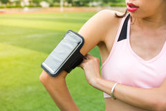 Smartphone создания девушки для того чтобы отслеживать jogging деятельность Стоковая Фотография RF