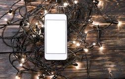 Smartphone с гирляндой рождества на деревянной предпосылке Стоковые Фотографии RF