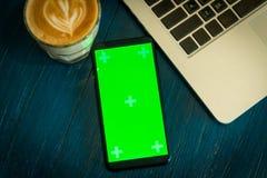Smartphone с зеленым экраном около горячих кофе и компьтер-книжки на деревянном столе Стоковое Изображение