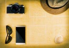 Smartphone с пустым экраном, соломенной шляпой, стеклами солнца, камерой фильма и раковиной на заднем плане желтого полотенца Ter стоковое фото