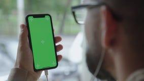 Smartphone с chromakey в руках человека с наушниками видеоматериал