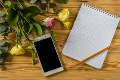 Smartphone, чистый лист бумаги, карандаш и eustoma на деревянной предпосылке Стоковые Изображения