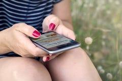 smartphone чтения женщины на траве Стоковое фото RF