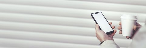 Χλεύη επάνω ενός smartphone και ενός πλαστικού φλυτζανιού με τον καφέ στα χέρια ενός τύπου σε ένα άσπρο υπόβαθρο στοκ εικόνες