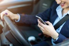 Женщина используя смартфон пока управляющ автомобилем стоковые изображения rf